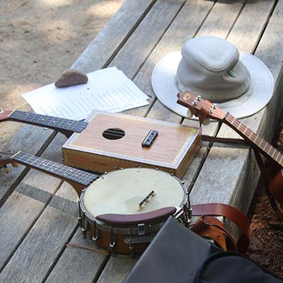 A variety of musical instruments and a floppy hat sit on a bench in the sun