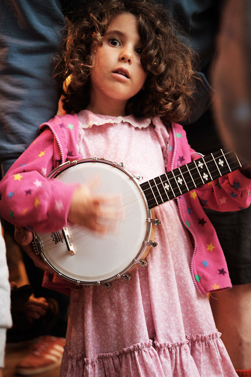 A young girl plays the banjo